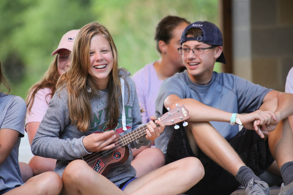 Camper strumming a ukelele during a Stage Night performance