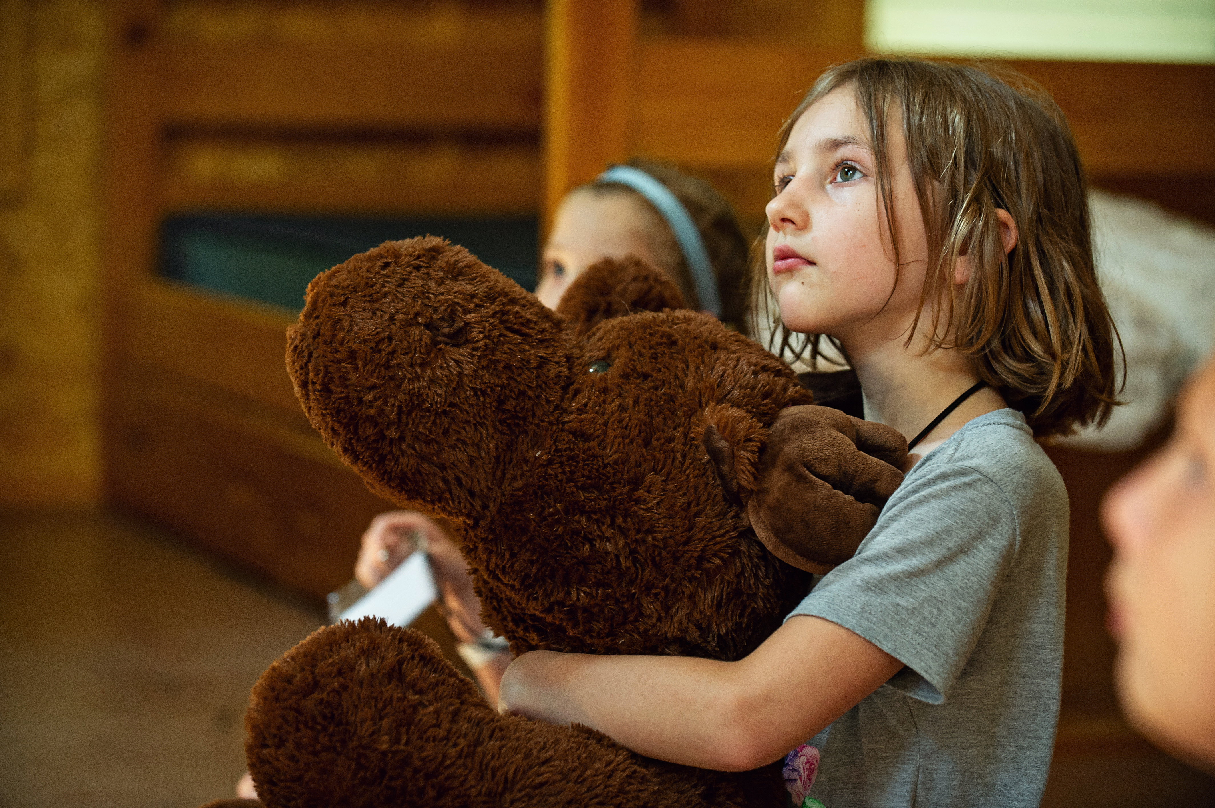 A camper hugging a giant teddy bear listening intently during Cabin Chat
