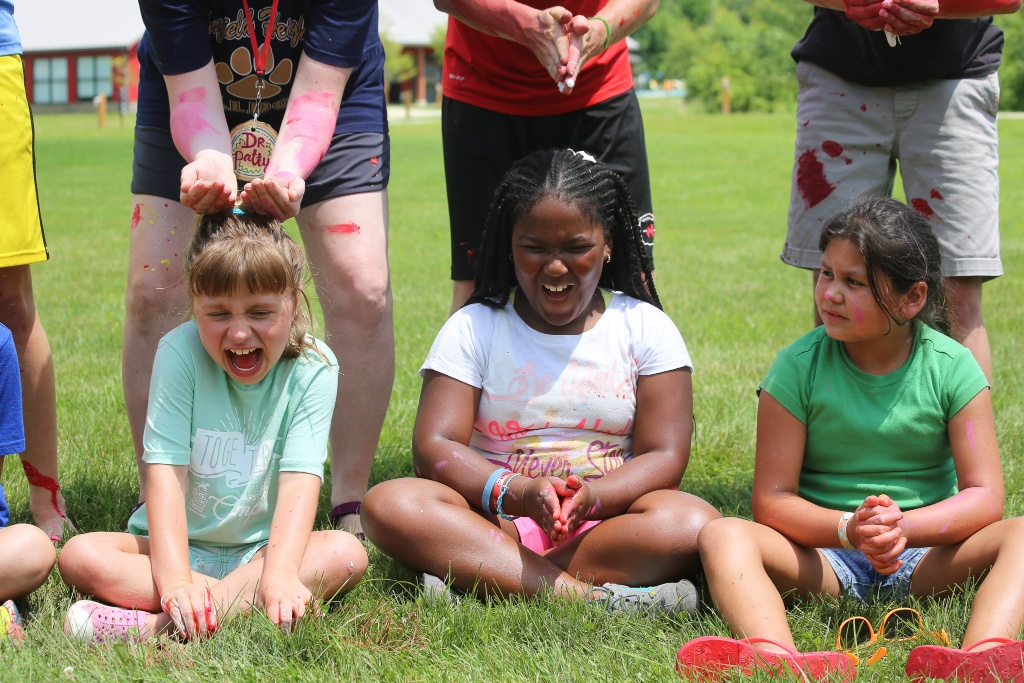Three campers laughing as Icky Silly supplies are placed on their heads.