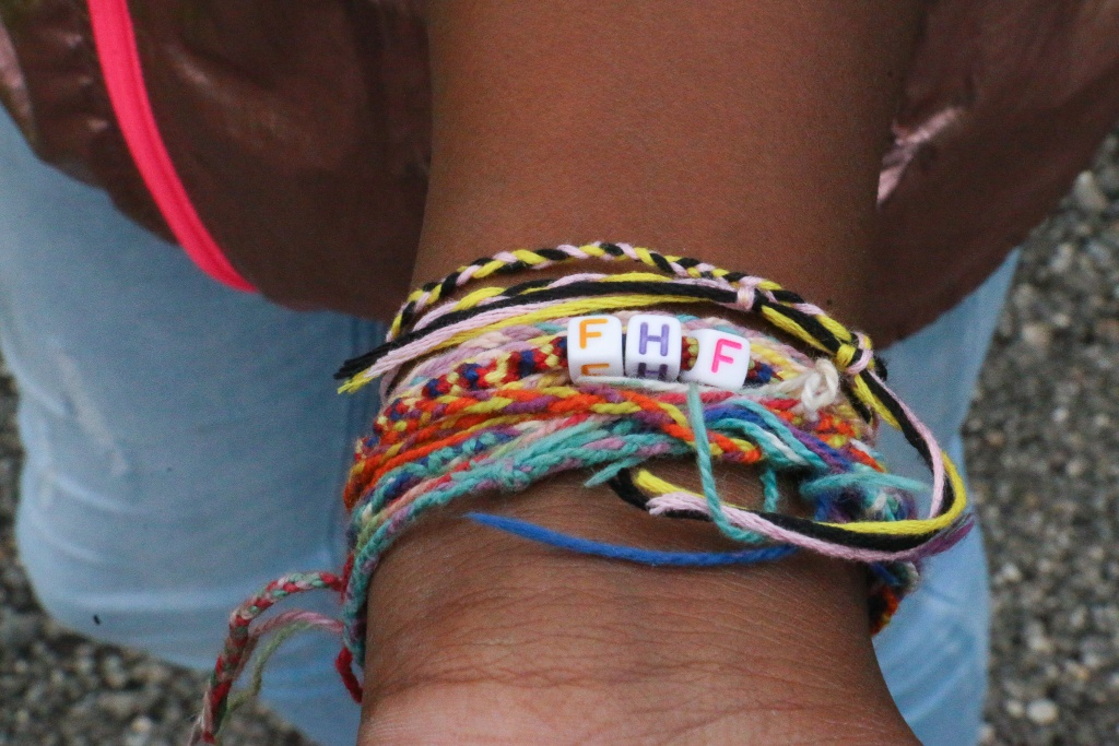 Wrist of camper with yarn bracelets from web of gratitude activity