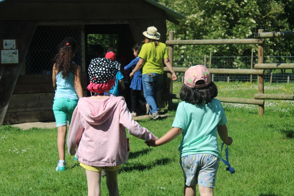 Two young campers holding hands walking towards the activity barn at L'Envol, the SeriousFun camp in France