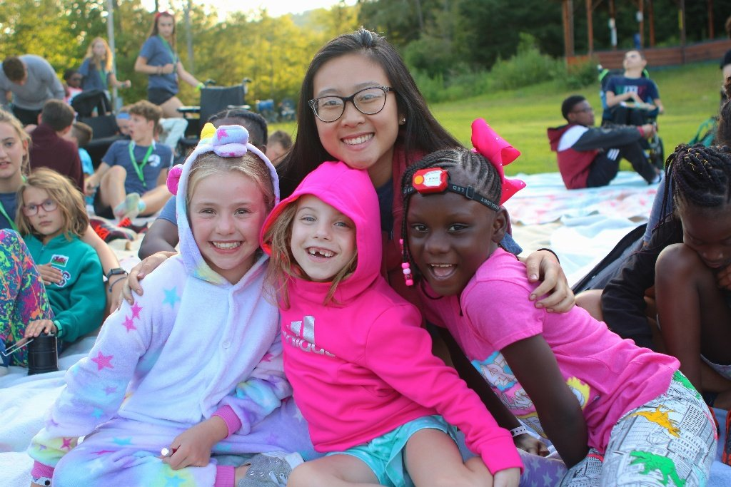 Three happy campers with a volunteer outside at a pajama party at Double H Ranch, the SeriousFun camp in New York