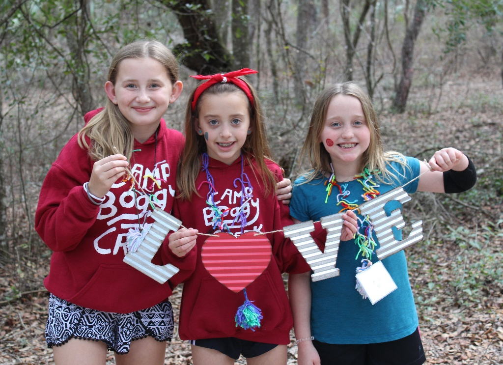 Three campers holding letters to spell LOVE at Camp Boggy Creek, the SeriousFun camp in Florida