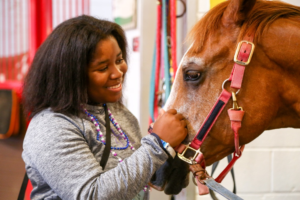 A camper looking lovingly at a horse at Victory Junction, the SeriousFun camp in North Carolina